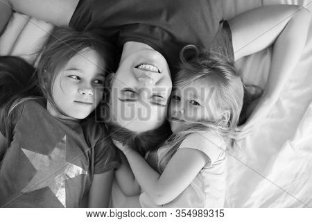 Mum And Two Daughters Lying On The Floor. White Background. Black-white.