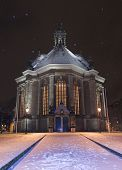 the new church in the hague / nieuwe kerk den haag covered in snow at night, while snowing. this church was build in the 17th century. it is a typical example of early protestant architecture. the grave monument of spinoza can be found in the garden of th poster