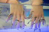 close-up of hands taking care at fish spa poster