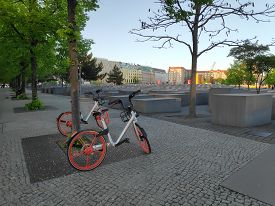 Berlin, Germany - April 29, 2019: Orange Coloured Rental Cycles Parked Along The Holocaust Memorial
