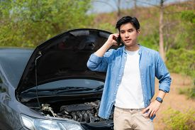 Asian Young Unhappy Man Talking On A Cell Phone  In Front Of The Open Hood  Broken Down Car On Count
