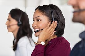 Multiethnic colleagues working. Team of business people sitting in a row working in a call center. Smiling customer support operator at work. Middle eastern woman with headset working at helpdesk.