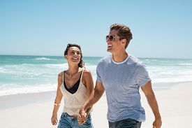 Happy young couple walking on tropical beach and laughing together. Joyful man and beautiful smiling woman holding hands in casual wearing sunglasses. Carefree couple in love have fun at seaside.