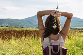 Beautiful Woman Walking In Nature. Happy People Lifestyle. Woman Holding Wild Flower In Sunshine. Na