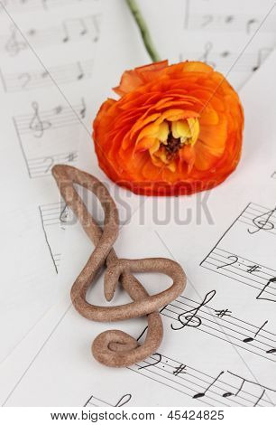 Treble clef and flower on musical background