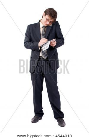 Young Businessman Calling By Cellular Phone And Writes In A Notebook