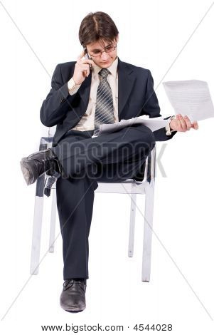 Young Businessman Looks Documents And Calling By Cellular Phone