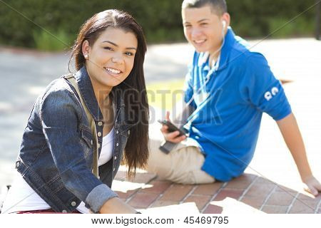 Girl And Boy Students Relaxing Outdoors