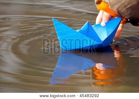Child's hand and blue paper boat in water in spring