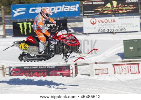 Red And Black Polaris Snowmobile Racing In Air