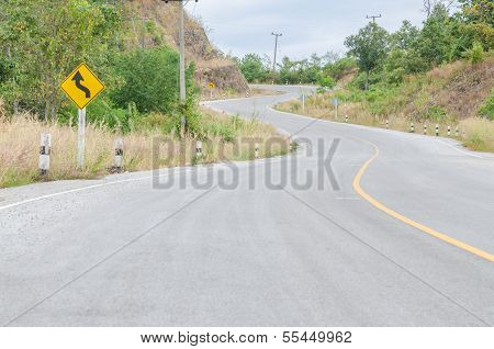 Twisty Mountain Road With Roadsign In Nature