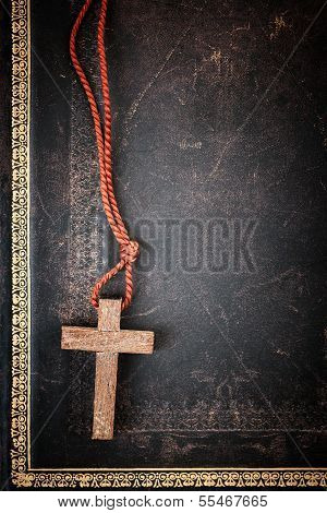 Closeup of simple wooden Christian cross necklace on holy Bible with copy space poster
