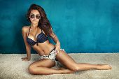 Summer photo of beautiful brunette woman posing in sunglasses and wearing swimsuit. poster
