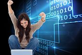 Composite image of pretty brunette cheering while using laptop poster