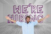 Handsome man raising arms in front of were hiring graphic in a grey room poster