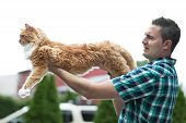 Man holding his cherished purebred Maine Coon cat outright to show his size. Shallow depth of field. poster