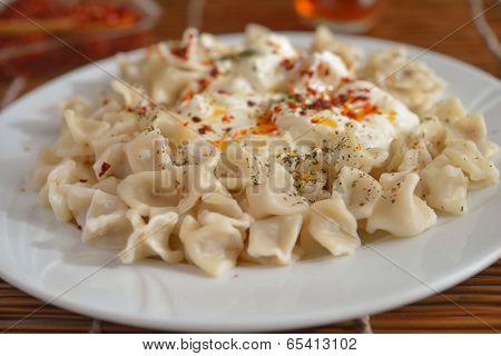 Turkish dumplings manti with strained yogurt and Aleppo pepper closeup poster