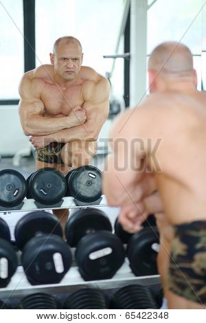 Middleaged bodybuilder in shorts looks into mirror at his muscles