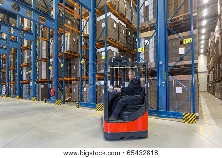 Man driving his reachtruck into a row with storage racks. In the storage racks there are cardboard boxes stored.