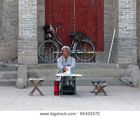 Inchuan, Inner Mongolia - Jul 6, 2011: Chinese Fortune Teller Sitting At The Entrance To A Buddhist