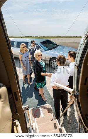 Airhostess and pilot greeting corporate people before boarding private jet