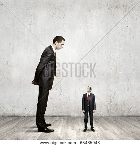 Big bossy businessman looking down at small businessman