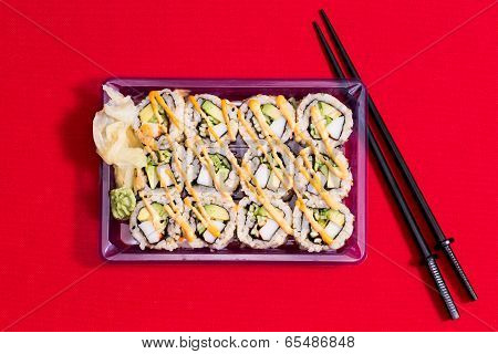 To Go Sushi Box On Red Table Cloth With Chopsticks