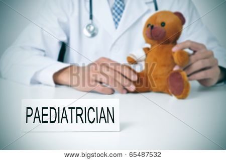 a doctor sitting in a desk with a injured teddy bear and a nameplate with the word paediatrician written in it
