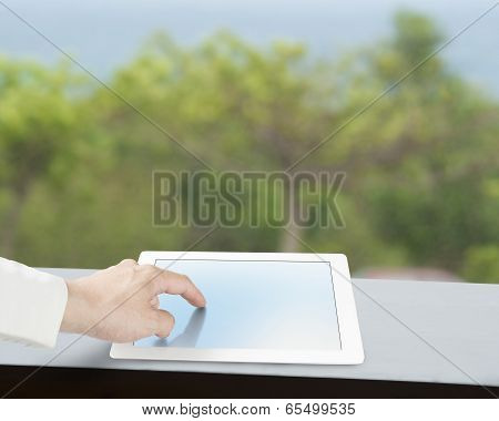 Touching Tablet On Table With Green Background