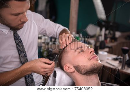 hairdresser  shaves with blade of razor  face of satisfied  client in  professional  hairdressing salon poster
