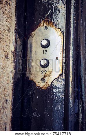 Two vintage doorbell buttons in the door of an old building
