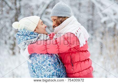 Portrait of happy girl in winterwear embracing her boyfriend outside