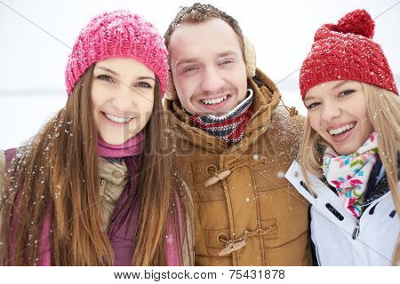 Group of happy friends in winterwear looking at camera outside
