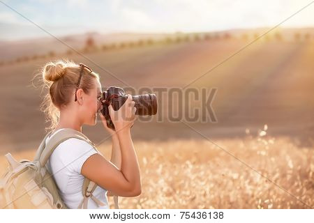Happy traveler girl photographing ripe wheat field in bright sun rays, autumn harvest season, interesting profession, travel and tourism concept poster