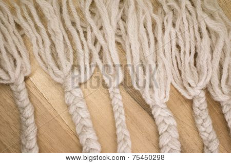 hand made woven wool braids on a wood surfaceclose up poster