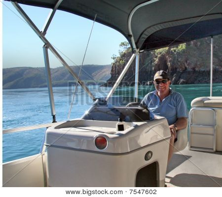 Man At Console Of Party Pontoon