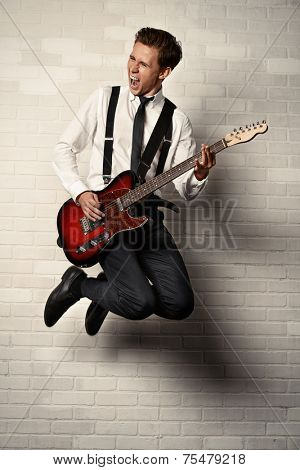 Expressive young man playing rock-n-roll music on his electric guitar. Retro, vintage style.