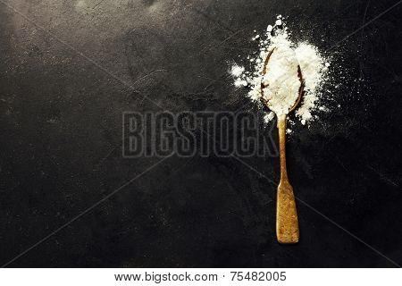 Whole flour in spoon on dark vintage background