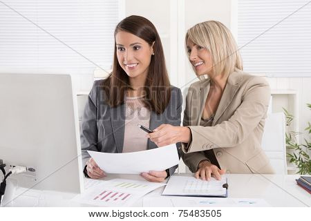 Two attractive business woman sitting together in a team in the office.