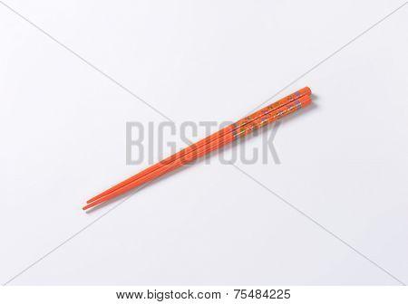 pair of orange chopsticks on white background