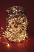Christmas lights in a jar on a red background. poster