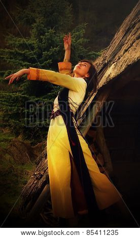 girl in a historical costume posing in a dramatic gesture amids the forest surroundings