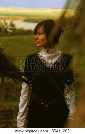beautiful young woman with dark hair and a black velvet historical dress walking through an open lan