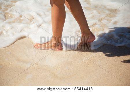 Legs Of A Woman On The Beach