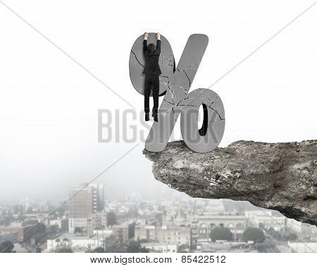 Businessman Hanging On Cracked Percentage Sign With Cliff Urban Scene