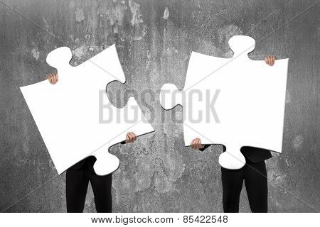 Two Business People Assembling White Jigsaw Puzzles With Concrete Wall