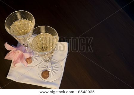 Two Waterford champagne Glasses with a Flower and Shells on a Table
