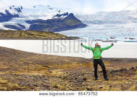 Hiking adventure travel man cheering happy on hike on Iceland. Hiker cheerful at glacier and glacial lagoon / lake of Fjallsarlon, Vatna glacier, Vatnajokull National Park. Icelandic nature landscape.