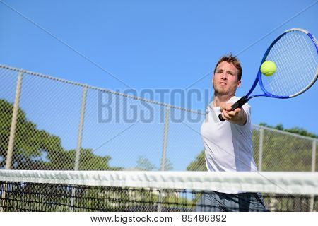 Tennis player man hitting ball in a volley. Male sport fitness athlete playing tennis on outdoors hard court in summer. Healthy active lifestyle concept.