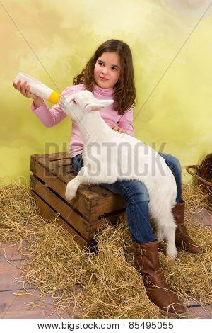 Lovely girl feeding a newborn baby goat with a milk bottle